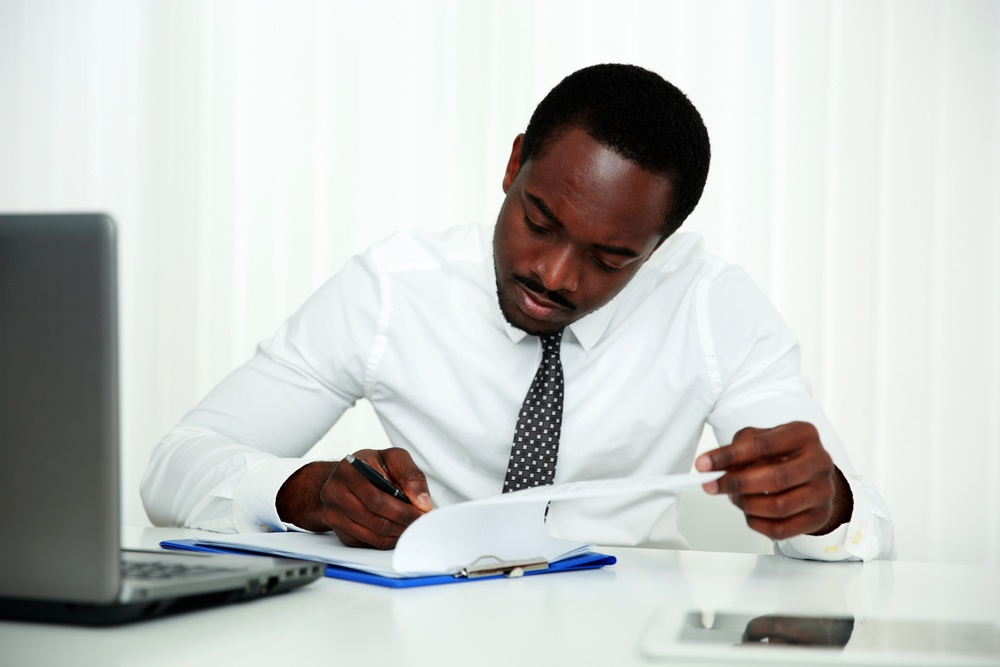 African man signing document in office.jpeg