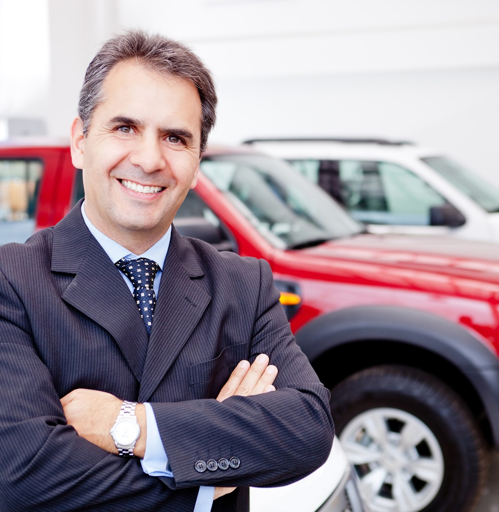 Business man working at a car dealer smiling.jpeg