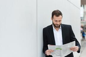 Businessman reading a newspaper on his lunch break as he leans against a white wall with copyspace.jpeg