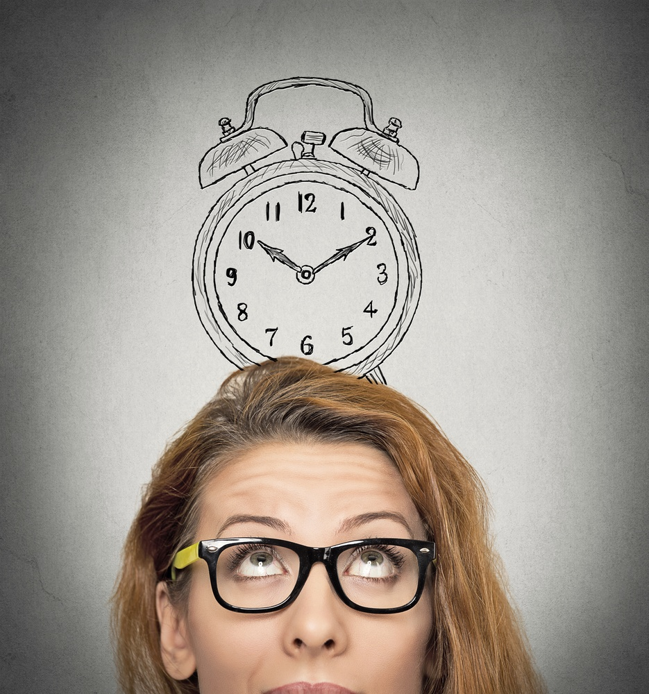 closeup headshot young business woman with alarm clock drawing sketch above her head, isolated grey wall background. Human face expressions, emotions. Time, punctuality, busy schedule concept.jpeg