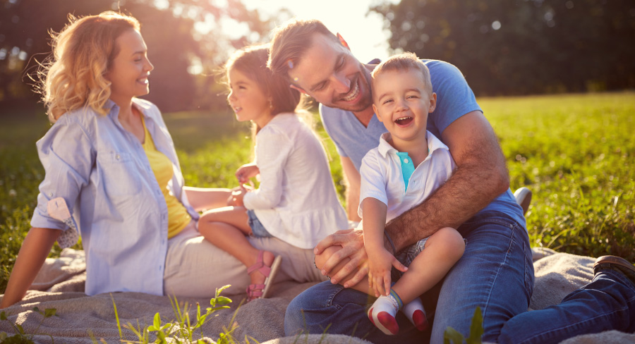 Happy family with mom and dad and two kids sitting on grass in sunlight.
